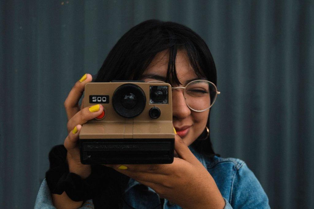 Female holding a polaroid camera.