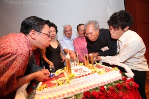Four FASS Deans, alumni and students blowing out candles on the anniversary cake