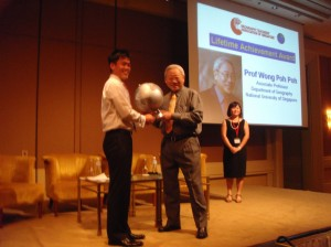 The Chairman of the Geography Teachers' Association of Singapore, Mr Josef Tan, presents a gift to Associate Professor Wong Poh Poh during the Lifetime Achievement Award ceremony