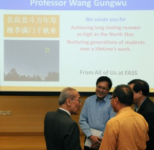 Prof Wang mingles with guests after the lecture with a special message from FASS onscreen behind