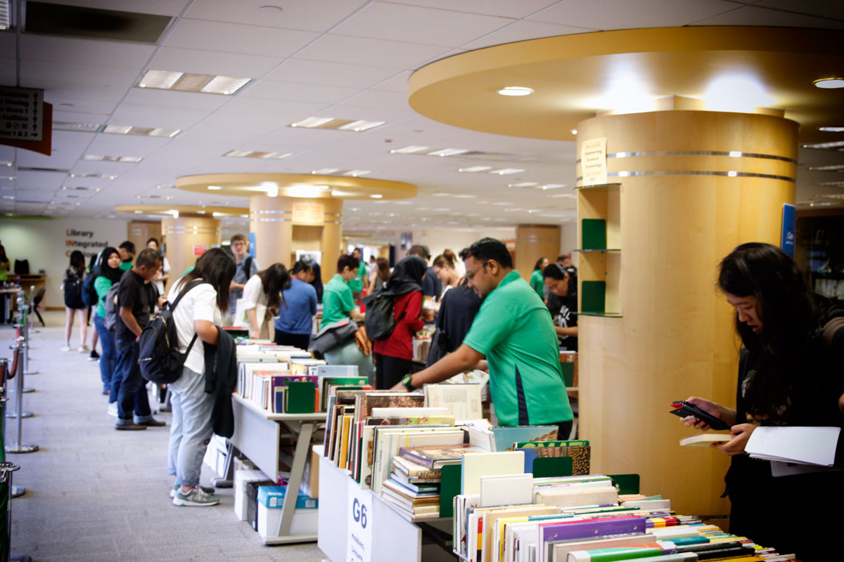 Enthusiastic students and staff browsing for pre-loved books to buy