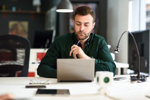 young-man-studying-with-laptop-computer-on-white-desk_1139-980.jpg