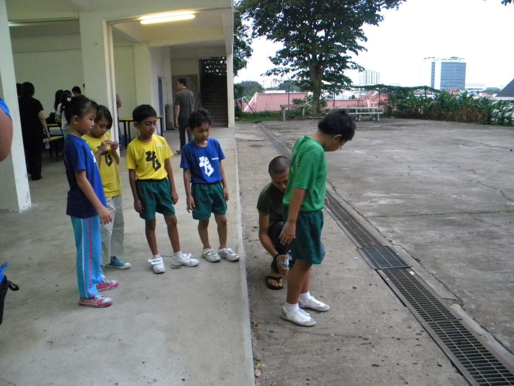 Andrew helping the children spray repellant