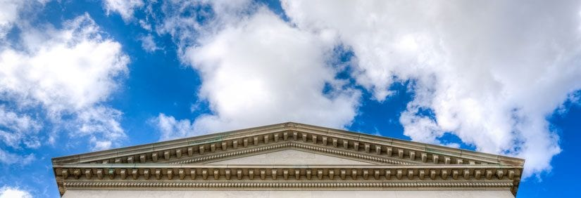 Big blue sky and fluffy clouds float behind the iconic Dallas Hall building.