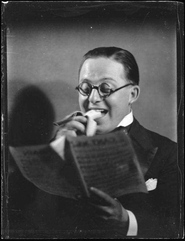 Glass plate negative of Eric Sheldon eating a banana and reading sheet music, 1934