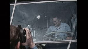 driver in bus with bullet hole in the windshield