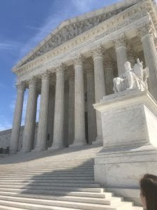 Exterior of Supreme Court steps with bright sun and clouds behind it.