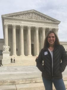 Ashley stands in front of the Supreme Court with her hands in her coat pockets.