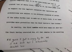 """Excerpt from typed page: ...Justice complains that it is the undue burden test that is crested """"out of whole cloth."""" [word crossed out, replacement indistinguishable] as is, the Chief [""""Judge"""" crossed out, """"Justice"""" handwritten] sites no support for his implicit [indistinguishable word] that regulations and prohibitions are subject to two different standards of review. If the undue burden test is made out of whole cloth, it at least provides more protection than the Chief Justice's """"new clothes."""" In reality, the Chief [""""Justice"""" crossed out] would have women sit shiv'sh -- the Court having overruled Roe, all that remains is the unveiling... Handwritten note at bottom of page: *I guess I got so angry by the end of the draft that I subconsciously denoted him."""