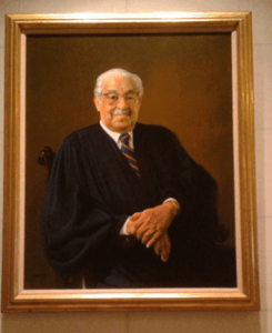 Thurgood Marshall sits in his Justice robe and a blue and orange striped tie, right hand resting on top of his left wrist.