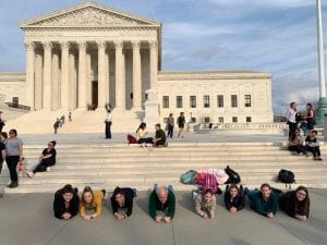 7 students and Professor Koblyka hold a plank position with their faces towards the camera. The Supreme Court steps are in the background.
