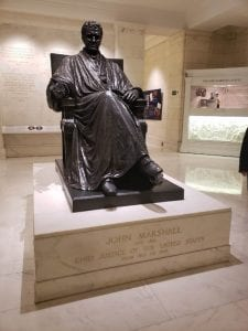 Bronze statue of John Marshall sits seated in his Justice robe. Sculpture sits on a marble bed with the description engraved in gold.