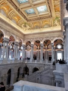 View of two floors - two marble staircases lead up to a windowed gallery. Ornate murals decorate the ceiling, along with etched glass skylights.