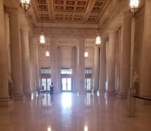 Hall with Marble floors, walls, and columns. In between the columns are busts.