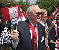 Robert Hyer Thomas '53, grandson of founding President Robert Stewart Hyer, waves a miniature centennial flag.