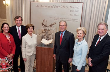 SMU trustees honored George and Laura Bush (center) by acquiring a historic journal for DeGolyer Library. The presentation included (from left) Dean of Central University Libraries Gillian McCombs, SMU President R. Gerald Turner, Trustee Chair Caren Prothro, and DeGolyer Director Russell Martin.