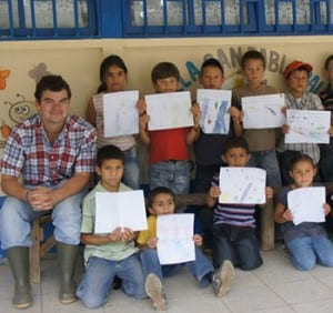 Jonathan Lane (left) with children showing off their artwork created in conjunction with a river clean-up project.