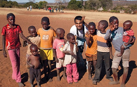 SMU junior Prithvi Rudrappa takes five with a group of children on a soccer field in Simoonga, a village near Livingstone, Zambia. Photo by Katie Bernet.