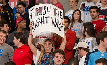 An SMU student raises a sign with the catchphrase the Mustangs used to end their season at home.