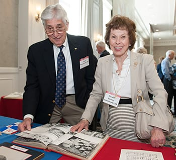Tom and Susan Downs Armstrong '59 reminisced while leafing through old Rotunda yearbooks at the Golden Mustangs reunion April 10.