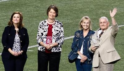Gary Jackson waves to the crowd after receiving the Lindale ISD Distinguished Alumni Award. Pictued with him are (from left) Mitzi Bjork, Lindale ISD Alumni Association president; Lindale DAA recipient Carolyn Todd; and Mrs. Jackson. Photo by Larry Wilson.