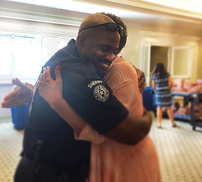 A sheriff's deputy receives a hug at the Human Rights Dallas summit July 9 at SMU.