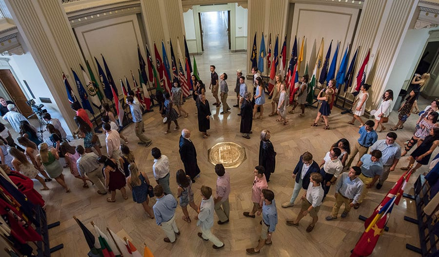 Alumni Marshals direct students around the SMU seal in Dallas Hall during Rotunda Passage, a beloved part of the tradition of Opening Convocation.