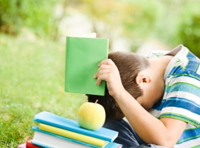 Stock photo of a boy tired of reading