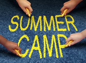 Stock art of 'summer camp' spelled out in chalk surrounded by kids' hands