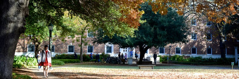 SMU students walking outside a residence hall, fall colors