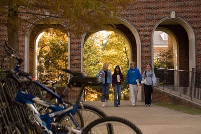 Students on campus with bikes, fall