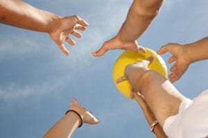 Stock photo of hands reaching for a volleyball