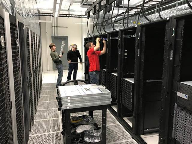 Equipment is installed in the appropriate predefined location in each of the 22 cabinets housing the new Maneframe II HPC Cluster.