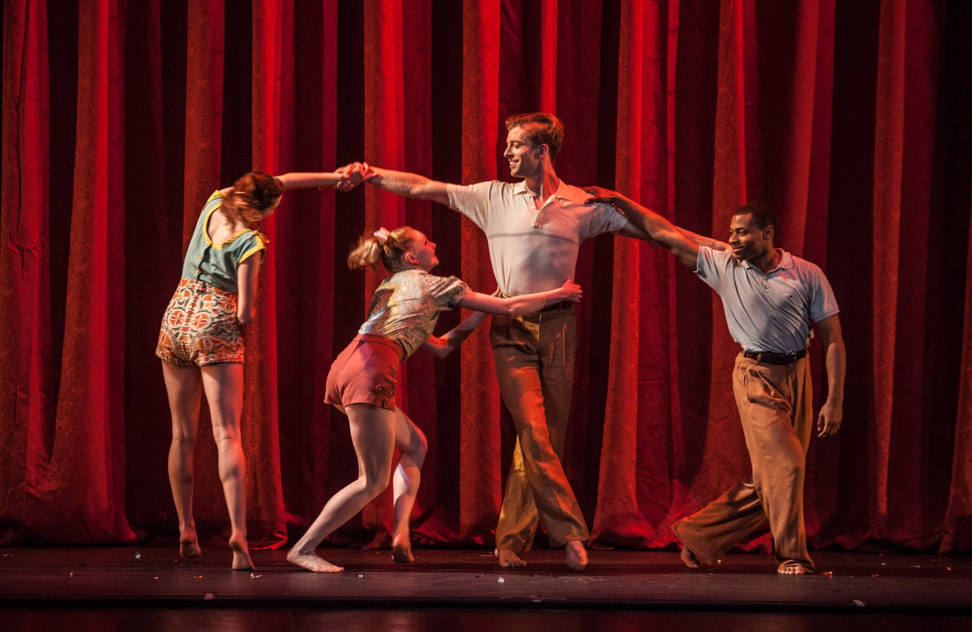 group of dancers in front of a red curtain