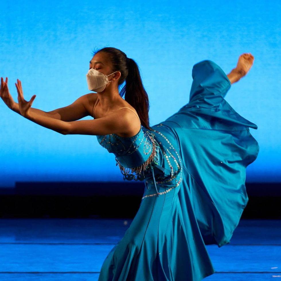 female dancer in blue dress against a blue background