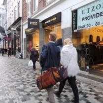 A stylish couple walks along Stroget, a popular street for shopping in Copenhagen.