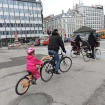 A little girl and her father bike around Nørreport Station in Copenhagen