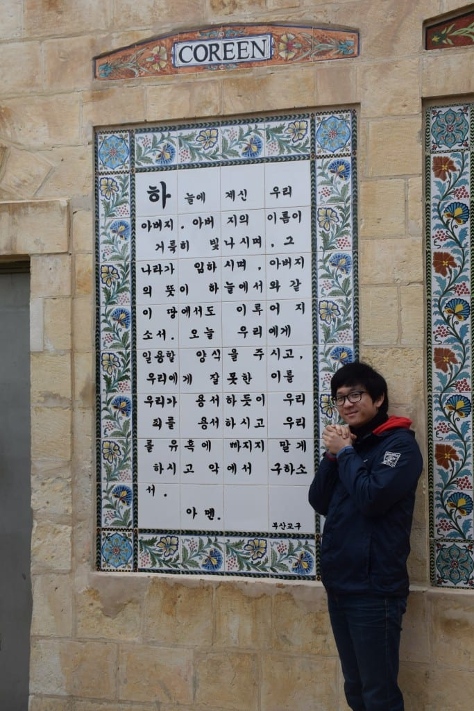 Perkins student Sungmoon Lee, pictured in the courtyard of the Church of the Pater Noster (Our Father), by The Lord's Prayer written in the Korean language.