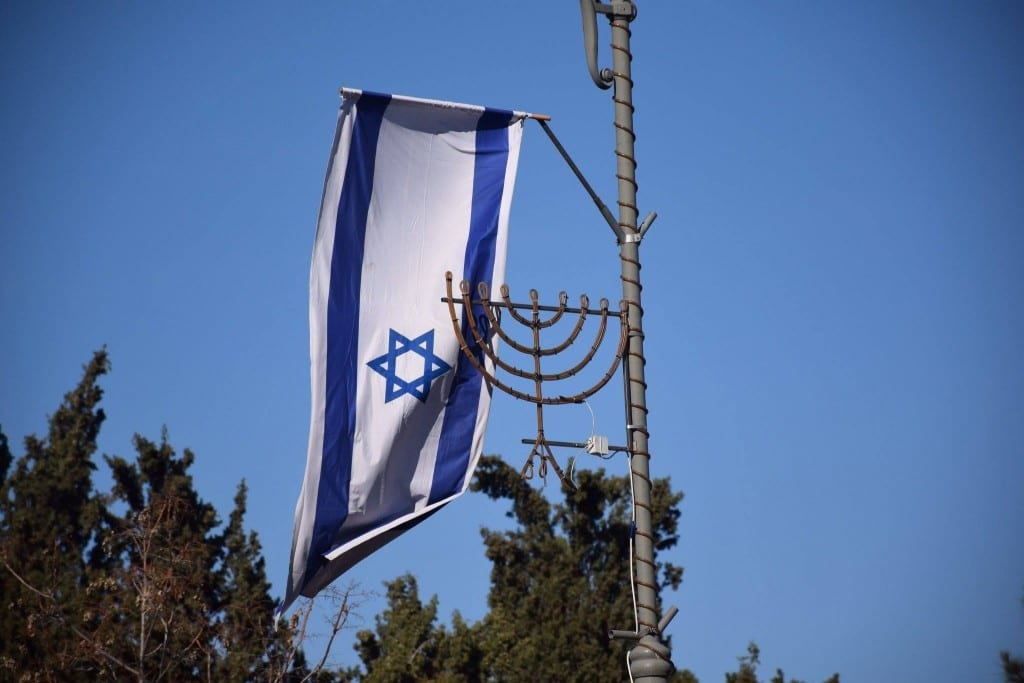 The flag of Israel waves in the breeze over the city.