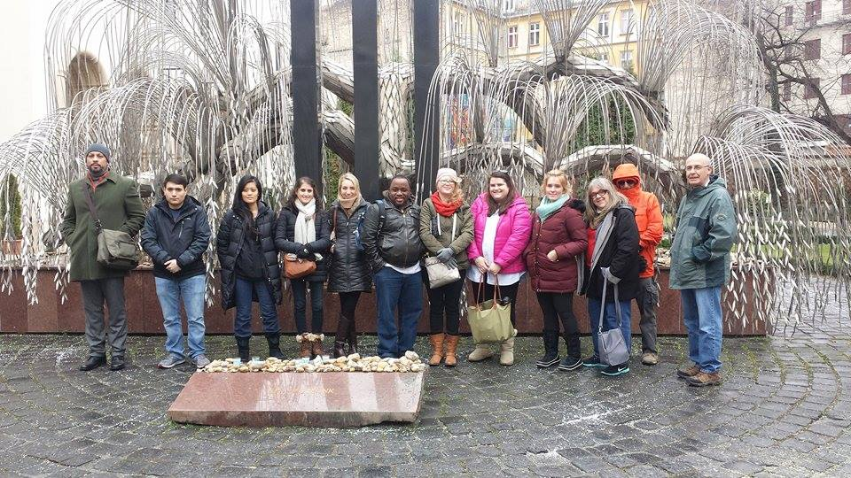 """The SMU Embrey Human Rights Program pilgrims in Budpest, Hungary,  stand in front of a weeping willow-inspired artwork known as the """"Tree of Life""""/""""Emanuel Tree"""" — a powerful tribute to thousands of  Holocaust victims buried nearby. The  memorial, by artist Imre Varga, was sponsored by the Emanuel Foundation, created by actor Tony Curtis to honor his Hungarian-Jewish roots. Photo shared by Amber/SMU Adventures."""