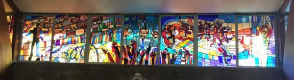 A stained glass window in the Regina Mundi Church, depicting the killing of young Hector Pieterson during the Soweto Uprising.  Nelson Mandela is in the center frame, with barbed wire at the bottom left.