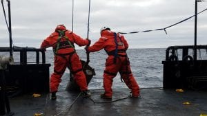 Rob Harris and the ships Bowson, Jim, deploying the heat flow probe at our very first site. Any time we're out on the deck working we have to have on these big orange mustang suits to keep us warm in the freezing temperatures when very cold water is often splashing up onto the deck.