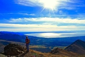 Dr. Matt Hornbach at the top of Wolverine Peak with Cook Inlet and the Alaska Range in background.