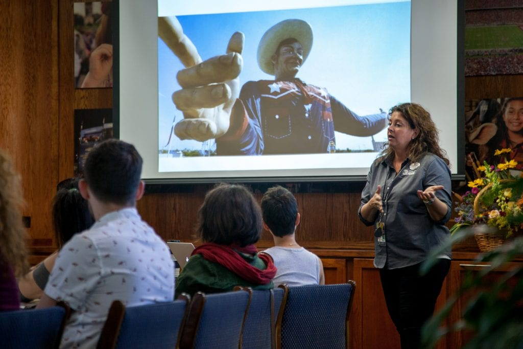 Adjunct professor Jennifer Schuder, senior vice president of marketing for the State Fair of Texas, talks with students at the State Fair administrative offices
