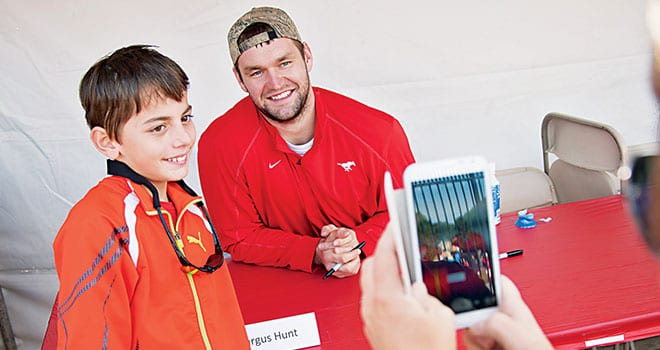 Mustang defensive star Margus Hunt '13 (right), drafted just days later by the NFL's Cincinnati Bengals, was among players who signed autographs and posed for photos with fans.
