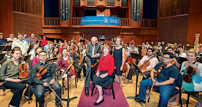 (Center, L-R) Maestro Paul Phillips, Martha Raley Peak '50 and Martha Peak Rochelle '76 surrounded by members of the Meadows Symphony Orchestra at a ceremony announcing the Martha Raley Peak Endowed Centennial Chair and Director of the Meadows Symphony Orchestra.