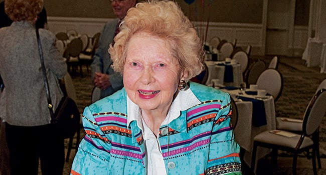 """Catherine B.""""Kitty"""" Wilson '45 leafed through a Rotunda during the Golden Mustangs Reunion on April 16."""