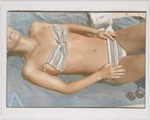 Striped suit, 1977, Photograph of the torso of a sunbathing woman wearing a striped bikini.