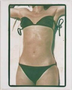 Green suit, 1976, Photograph of the torso of a sunbathing woman wearing a green bikini.