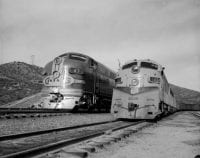 Santa Fe No. 47 DE-P passenger train and Union Pacific No. 1434 freight wait at Summit, CA in Cajon Pass., 1915, DeGolyer Library, SMU.
